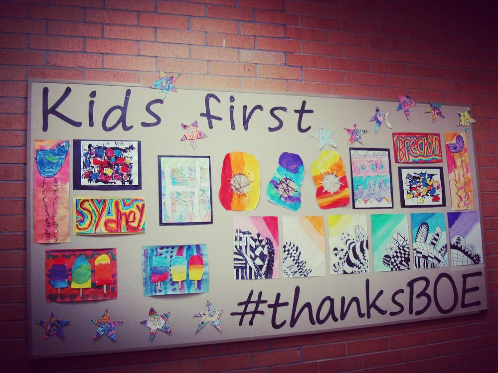 Bulletin boad that says Kids First thanks board of education with art projects from elementary students